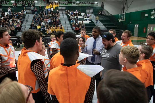 West Bloomfield High School percussion band instructor Evan Hall, center, and director Chris Vilag, center right, lead the pre-game ritual before the band prepares to perform for family and friends at the school gym Thursday in West Bloomfield Township.