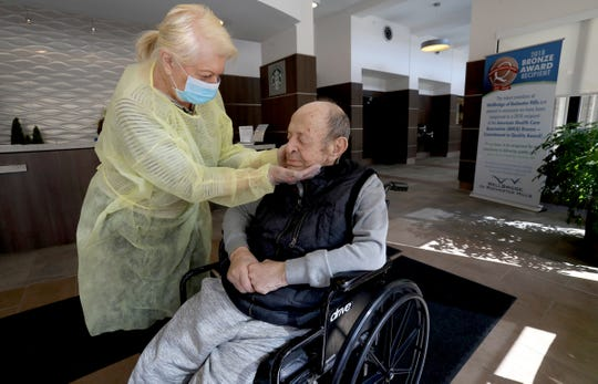 With gloves, mask and gown on, Johanna Mannone, 79, caresses her husband, Mike, in the front room of WellBridge of Rochester Hills on Friday. Johanna was given onetime, special permission to see her husband, who has been in the facility after suffering two strokes. She doesn't know when she'd get to see him again.