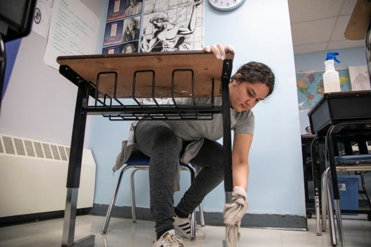 Detroit's Cesar Chavez Academy High School alumni Elizabeth Cardona, 21, a senior in social work at Saginaw Valley State University, chips in to deep clean her alma mater while she too is on break as schools prepare for the Coronavirus threat Friday, March, 13, 2020.