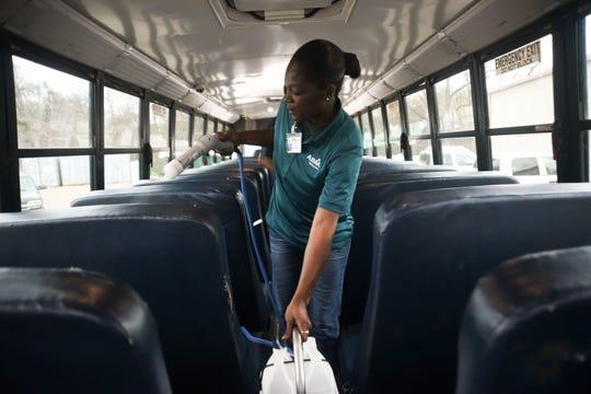 Regina Jones, with American Building Maintenance, disinfects a Vicksburg Warren School District school bus to combat the coronavirus, Friday, March 13, 2020, in Vicksburg, Miss.