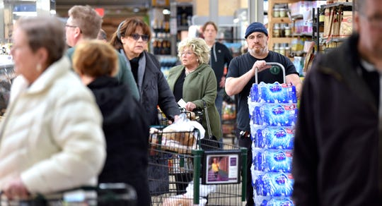 Shoppers and employees navigate the isle ways near the fresh-meat counter. People shop at the Village Market in Grosse Pointe Farms, Friday afternoon, March 13, 2020.