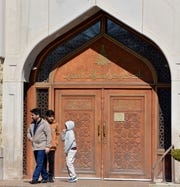 Three people who did not want to be identified, walk away from the locked, front doors of the Islamic Center of America in Dearborn Friday.