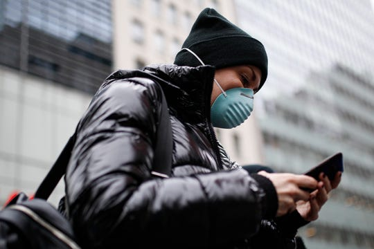 Pedestrian uses her phone while wearing a face mask in Herald Square, Thursday, March 12, 2020, in New York.