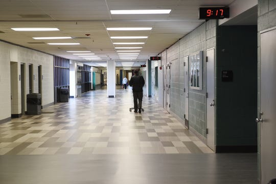 A teacher walks through an otherwise empty hallway at West Bloomfield High School on Friday, March 13, 2020. Students were asked to stay home, while educators used Friday to prepared to to teach students online due as a coronavirus precaution.
