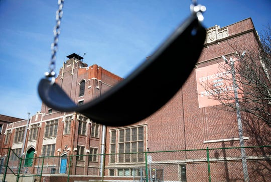 In this March 7, 2020 file photo, a swing sits empty on a playground outside Achievement First charter school in Providence, R.I. The public charter school, like a nearby Catholic school, closed after a teacher who attended the same Italy trip awaited test results for the new coronavirus. Many parents are now deciding how to talk to their children about the virus.