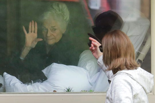 Judie Shape, left, who has tested positive for the coronavirus, waves to her daughter, Lori Spencer, right, as they visit on the phone and look at each other through a window at the Life Care Center in Kirkland, Wash., near Seattle on March 11, 2020. In-person visits are not allowed at the nursing home.