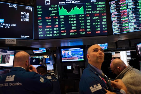Traders listen at the New York Stock Exchange to President Donald Trump's televised speech from the White House, Friday, March 13, 2020, in New York.