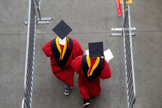 FILE - In this May 13, 2018, file photo, new graduates walk into the High Point Solutions Stadium before the start of the Rutgers University graduation ceremony in Piscataway Township, N.J.