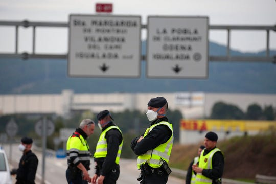 Mossos de esquadra police officers stand on the closed off road near Igualada, Spain, Friday, March 13, 2020. Over 60,000 people awoke Friday in four towns near Barcelona confined to their homes and with police blocking roads.