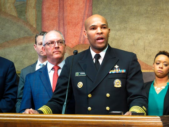U.S. Surgeon General Jerome Adams speaks about the new coronavirus, while Louisiana Gov. John Bel Edwards, left, listens on Thursday, March 12, 2020, in Baton Rouge, La. The number of cases of the COVID-19 disease caused by the virus are on the rise in Louisiana. (AP Photo/Melinda Deslatte)