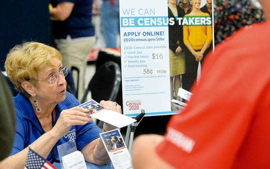FILE - In this Oct. 2, 2019 file photo, Joyce Dalbey, left, with the U.S. Census Bureau, talks to attendees at the Yuma Community Job & Education Fair inside the Yuma Civic Center about possible job opportunities with the federal agency, in Yuma, Ariz.