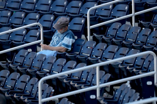 A lingering fan sits behind home plate after a spring training game between the New York Yankees and the Washington Nationals.
