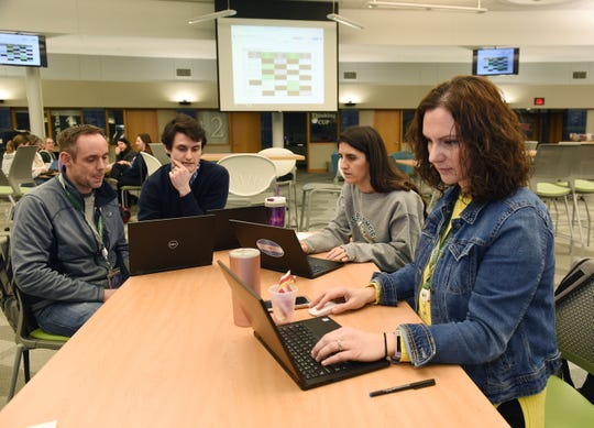 Lorig Bishop, language teacher, foreground, William Bishop, from left, Andrew Paniagua and Nuri Bye, all language teachers, prepare their online classes and lessons for their students at West Bloomfield High School.
