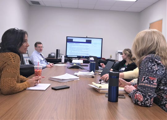 Chemung County Public Health Director Peter Buzzetti, second from left, and other Health Department staffers participate in a conference call about COVID-19 Friday with representatives from the state Health Department and health officials from other counties.