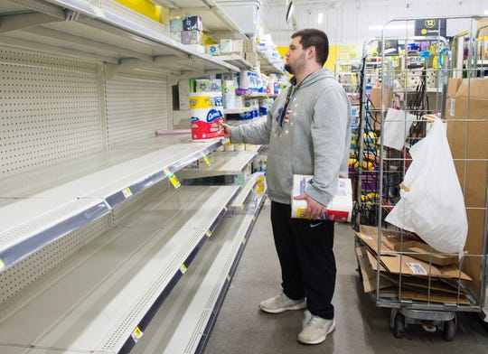 Employee Austin Cravens stares at shelf tags perplexed while stocking the last of the toilet paper available at Dollar General on Upper Mount Vernon Rd., Friday afternoon, March 13, 2020. Friday afternoon, March 13, 2020. The store has seen a major run on disinfectants, toilet paper and other household items due to the treat of the coronavirus.