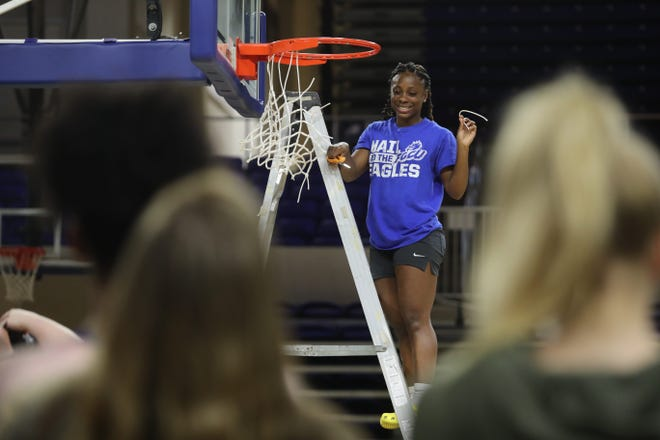 The FGCU women's basketball team celebrates the sudden end to their season with a net-cutting ceremony following the announcement that the rest of post-season games were canceled because of COVID-19.