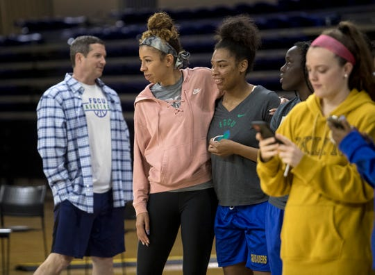 FGCU assistant basketball coach Chelsea Lyles comforts Tytionia Adderly at Alico Arena on Friday, March 13, 2020. The basketball team decided to celebrate the sudden end to their season with a net-cutting ceremony following the announcement that the rest of post-season games were canceled because of COVID-19.