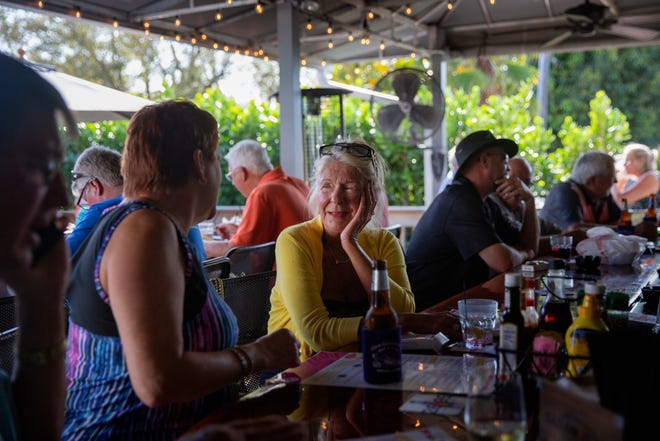 Monica Hopkins, left, a seasonal Naples resident from Hawley, Pennsylvania, talks with her friend Kathie Szkolar, center, of Naples, Thursday, March 12, 2020, at Alice Sweetwater's Bar & Grill in North Naples.