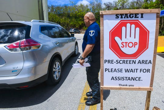 Security officer Ricky San Nicolas allows occupants in a vehicle to proceed through the stage one checkpoint and toward the Guam Memorial Hospital emergency room, Friday after acquiring information on their current health status and recent travel history.