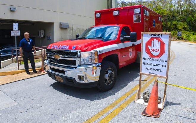 A Guam Fire Department ambulance prepares to depart from the stage one checkpoint, set up near the Guam Memorial Hospital emergency room, on Friday, March 13, 2020. Due to coronavirus concerns, the new measure to  pre-screen ER visitors, to include asking occupants of vehicles on their current health status and recent travel history, prior to proceeding through to the hospital's emergency room entrance.
