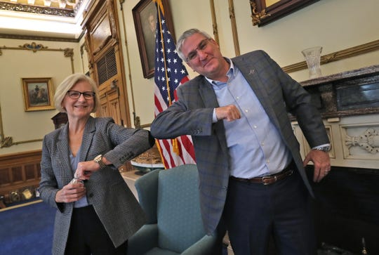 Indiana State Health Commissioner Dr. Kris Box, left, and Governor Eric Holcomb do elbow bumps after speaking to the media in his Indiana Statehouse office about COVID-19, Friday, March 13, 2020.