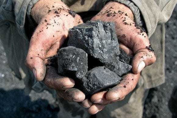 A miner holding coal nuggets in his cupped hands.