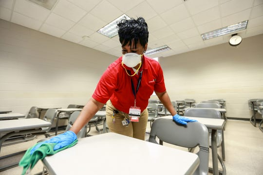 Debora Summers, supervisor of Services for Education disinfects desks in Dollye E. Robinson Liberal Arts building on the campus of Jackson State University in Jackson, Thursday, March 12, 2020.