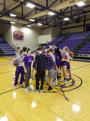 Bethel University's women's basketball team has one final team huddle on the court moments after head coach Chris Nelson told them the NAIA tournament had been canceled.