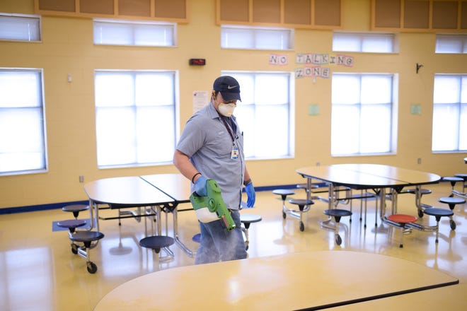 Knox County Schools worker Lonnie Johnson sanitizes the cafeteria with an electrostatic sprayer at Brickey-McCloud Elementary in Knoxville, Tenn. on Friday, March 13, 2020. Knox County Schools, after closing due to coronavirus concerns, is disinfecting all of its 93 schools using different cleaning methods such as traditional wiping-down surfaces to using modern electrostatic sprayers.