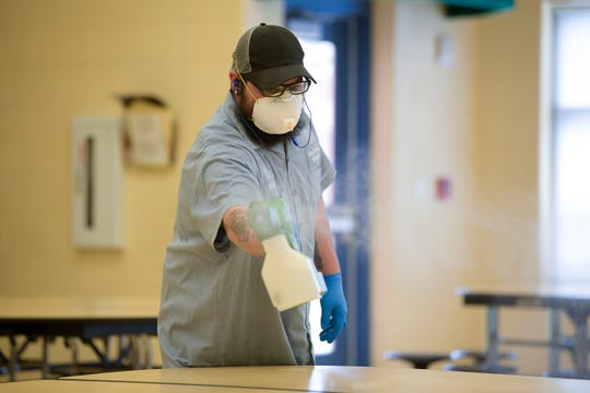 Knox County Schools worker Richard Frazier sanitizes the cafeteria with an electrostatic sprayer March 13 at Brickey-McCloud Elementary in Knoxville.
