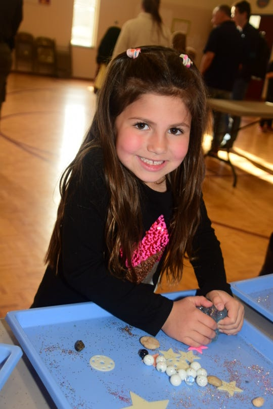 Maizey Baster, 5, enjoys squishing Galaxy Dough through her fingers at an exhibit provided by The Muse Knoxville at Ball Camp Elementary's STEAM Night March 11. 2020