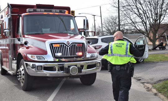 Lancaster Police Officer Adam Dilley puts on his high-visibility vest as he walks to the scene of a crash on East Main Street March 13. Lancaster firefighters were already on scene treating passengers in the car. On March 17, Lancaster residents will vote on a levy to increase income tax for the city's safety services.