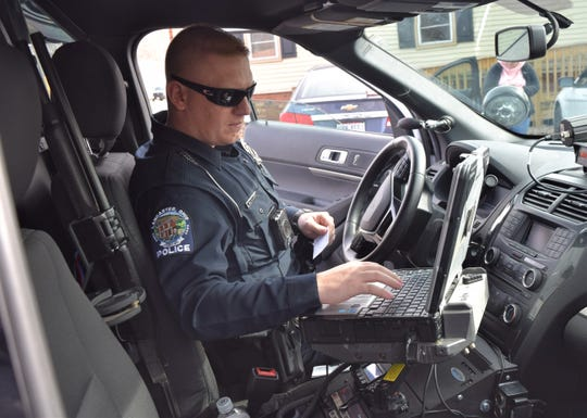 Lancaster Police Officer Adam Dilley types information into his patrol car's computer at the scene of a non-injury crash March 13. On March 17, Lancaster residents will vote on a levy to increase income tax for the city's safety services.