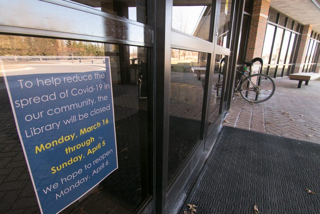 The Brighton District Library, shown Friday, March 13, 2020, posts a sign indicating that they will be closed from March 16 through April 5 due to the coronavirus.
