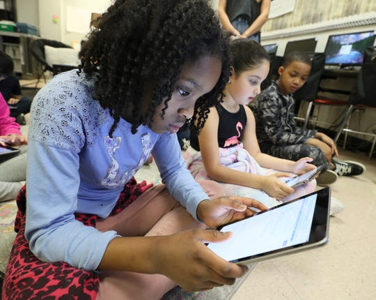 Sandra Wilson logs into a school-supplied iPad at Klondike Elementary on Friday. The third grade students in Rebecca Reynolds' technology class were preparing to get JCPS lessons remotely during the weeks that the students would not be attending school.