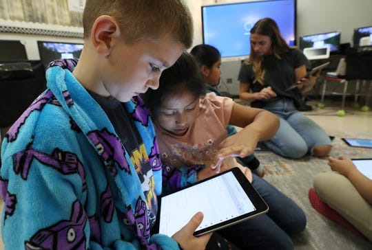 Riley Johnson and Kelly Escalona work together on a school-supplied iPad at Klondike Elementary on Friday. The third grade students in Rebecca Reynolds' technology class were preparing to get JCPS lessons remotely during the weeks that the students would not be attending school.