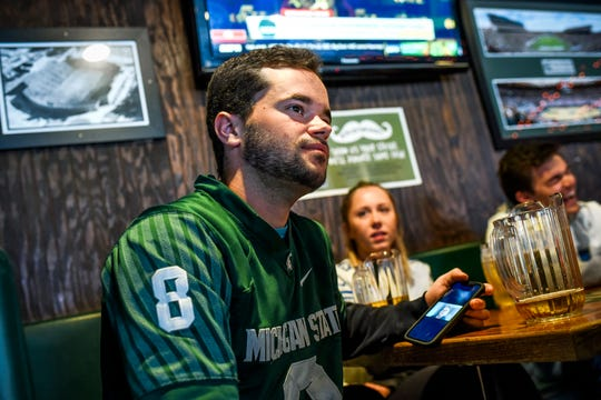 Michigan State University student Ben Hamer, 22, drinks with friends while using his phone to watch a video stream of his advertising class on Thursday, March 12, 2020, at The Riv in East Lansing. MSU put courses online to help prevent spread of the coronavirus.