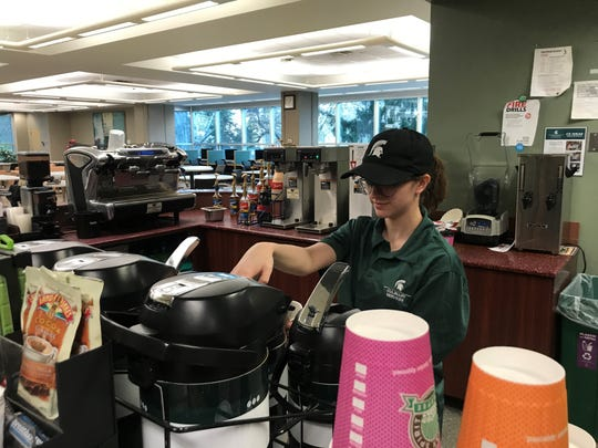 Emily Herbert, MSU senior and Sparty's store manager, works behind the counter at the main library location on Friday, March 13.