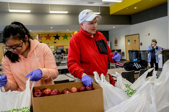 Melissa Washburn, right, a retired Lansing School District teacher, directs other volunteers to pack weekend bags of food for school district students Friday, March 13, 2020. This is a regular event that occurs every Friday and Washburn wants to continue it during the three-week break.