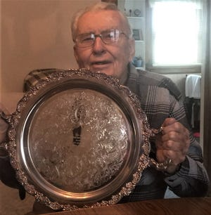 Lowell Sherer, 91, with his 2003 Antique Automobiles of America's Past President's Racing Cup award.