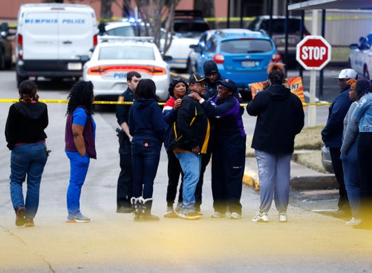 Family members gather outside home at the Canterbury Woods Apartments on Gallan Drive where a 9-year-old was shot and killed on Friday, March 13, 2020.