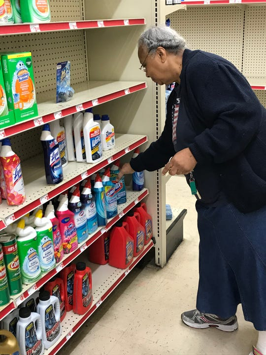 Brenda Cody stoops to pick-up cleaning supplies at a Frayser-area  Family Dollar