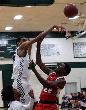 Milwaukee Academy of Sciences forward Darius Hannah blocks a shot by Racine Prairie's  Antuan Nesbitt during a Division 4 sectional semifinal at West Allis Hale Thursday night.