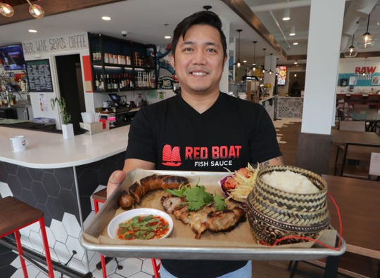Alex Hanesakda, owner of SapSap, holds a tray with sticky rice, lower right, Jeow Som, lower left, a spicy Loa dipping sauce, Lao sausage, lemon grass chicken, and papaya salad at SapSap, a Lao pop-up, caterer and wholesaler from Racine that is popping up at Crossroads Collective on North Farewell Avenue in Milwaukee on Wednesday, March 11, 2020.