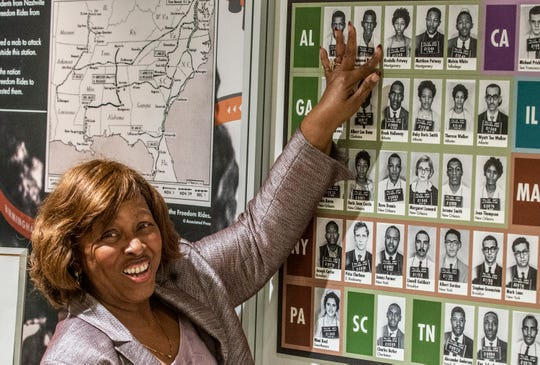 Kredelle Petway points to mugshots of herself, her brother and father on display at Montgomery's Freedom Rides museum on Thursday, March 12, 2020. She and her family were arrested as Freedom Riders who flew into Jackson, Mississippi's airport in 1961.