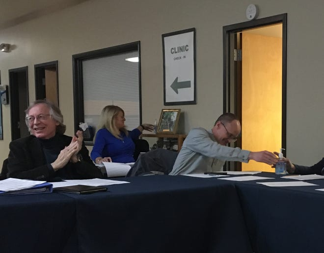 Delaware County Health Board members John Peterson, left, and David Grasso pass around a bottle of hand sanitizer during a meeting on Thursday, March 12.