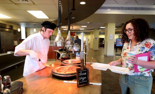 Jordan Benson, left, serves up a slice of pizza to MTSU freshman Geneva Taylor inside McCallie Dining Hall on Friday, March 13, 2020. Students have been encouraged to take meals to go as the university practices social distancing protocols as concerns over the coronavirus grow.