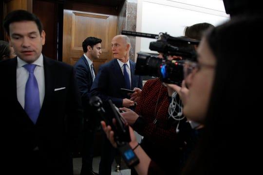 Sen. Rick Scott, R-Fla., center, looks back as he leaves a briefing on Capitol Hill in Washington, Thursday, March, 12, 2020, on the coronavirus outbreak, as Sen. Marco Rubio, R-Fla., speaks to the media at left.