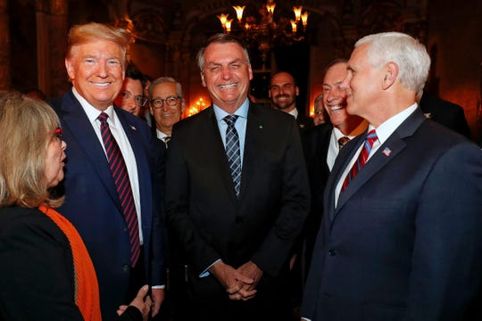 In this March 7, 2020 photo provided by Brazil's presidential press office, Brazil's President Jair Bolsonaro, center, stands with President Donald Trump, second from left, Vice President Mike Pence, right, and Brazil's Communications Director Fabio Wajngarten, behind Trump partially covered, during a dinner in Florida. Wajngarten tested positive for the new coronavirus, just days after the trip, according to Bolsonaro's communications office on Thursday, March 12, 2020.