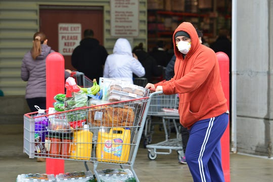 Brandon Urias, of Lodi, covers his face with a mask as he exits Costco with what he hopes is enough food for him, his wife and mother-in-law for two weeks. Panic shopping has caused traffic jams to enter the parking lot and long lines to enter the Costco in Teterboro, N.J. on Friday March 13, 2020.